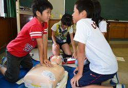 胸骨圧迫などを学ぶ児童