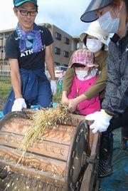 脱穀機での作業を体験する園児