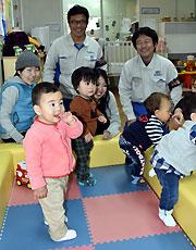キッズコーナーで遊ぶ子どもたちに笑顔を見せる