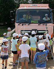 トラックの死角を確かめる児童たち