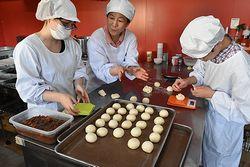 新商品の揚げパンを試作するメンバー