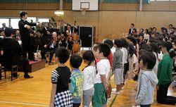 オーケストラの演奏で校歌を歌う児童