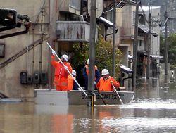 舟を使い昼食を届ける消防団員